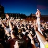 Des festivaliers levant les bras pendant un concert de musique.