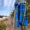 Tartan bleu et vert noué à un poteau le long d'une route rurale.