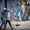 Deux hommes portant le masque traversent une intersection.