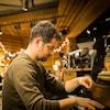 On voit l'artiste de profil, en train de jouer du piano, très concentrée.