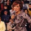 Lucille Dumont vêtue d'une robe fleurie, tenant un micro et chantant au Complexe Desjardins en 1977; en arrière plan flou, une foule assise
