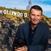 L'animateur sourit à la caméra. Derrière lui, on aperçoit la célèbre colline avec les lettres du mot «Hollywood» installées sur son flanc.