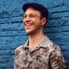 Un homme le dos appuyé sur un mur bleu, souriant, une chemise fleurie, des lunettes et une casquette sur la tête.