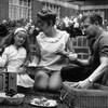 Une famille des années 60 pique-nique devant la maison