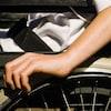 Plan serré d'une main manoeuvrant la roue d'un fauteuil roulant.