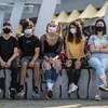 Des adolescents portant des masques assis sur une dalle de béton.