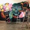 Mique Michelle est assise sur un escabot devant une murale qui dépeint une femme entourée de fleurs et de couleurs. En avant-plan : des cannettes de peinture à aérosol et d'autres escabots.