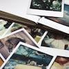 Une pile de vieilles photos en vrac à côté d'un album.