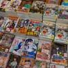 Des dizaines de magazines de mangas sont disposés côte-à-côte dans une boutique.