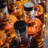 Des petites bouteilles d'un liquide foncé sont alignées sur une ligne de production, pas encore étiquetées.
