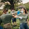 Une groupe d'hommes et de femmes portant des masques ramassent des déchets dans la nature.