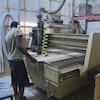Un ouvrier tient une planche de bois sur une machine industrielle.