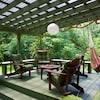 Quatre grands fauteuils et un hamac sur une terrasse entourée de verdure.