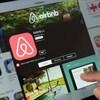 Un aperçu de l'application Airbnb sur une tablette où on voit le logo et une photo de piscine.