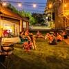 Un groupe d'adultes et d'enfants assis sur une pelouse verte alors que la nuit tombe et que la ruelle est illuminée.