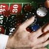 Un tapis de jeu de casino avec des jetons, et des mains en train de se saisir de tous les jetons