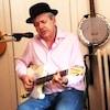 Un homme chante et joue de la guitare avec un chapeau melon sur la tête.