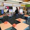 Une enseignante qui porte un couvre-visage se déplace dans une classe vide.