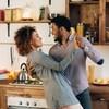 Un homme et une femme danse en couple dans une cuisine.