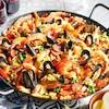 Une paëlla avec des moulles, des crevettes et du chorizo.
