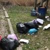 Plusieurs sacs à ordures et des déchets sur le sol.