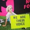 Une femme tenant une affiche disant «nous sommes leur voix» assise dans la pelouse.