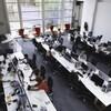 Un bureau à aire ouverte avec trois grandes tables où travaillent plusieurs personnes