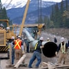 Des travailleurs sont sur le chantier d'un pipeline.