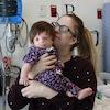 Une enfant atteinte du syndrome Treacher Collin dans les bras de sa mère à l'hôpital.
