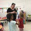 L'enseignante Gayané Deval est en classe avec trois élèves de maternelle devant un tableau.
