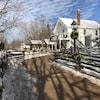 Un sentier clôturé garni de guirlandes de Noël avec une maison blanche en arrière-plan.