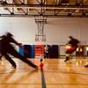 Des gens jouent au ballon chasseur dans un gymnase.