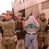 Des soldats  escortent deux hommes qui cachent leur visage.