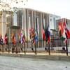 Des drapeaux de différents pays sont sur une clôture devant un édifice.