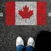 Vue en plongée de deux pieds arrêtés devant le dessin d'un drapeau du Canada sur le sol.