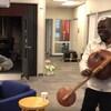 deux africains blacks dans les bureaux de Radio-Canada à Victoria un à casquette et qui danse, l,autre aqui souriant en jouant d'un instrument traditionel à cordes et calebasses.