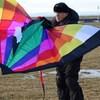 Un homme manipule un cerf-volant multicolore avant de le lancer dans les airs.