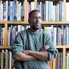 Un homme est debout les bras croisés, avec une bibliothèque derrière lui.