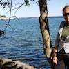 Une femme se tient debout, souriante, devant le lac Ontario.