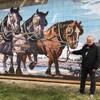 Peinture murale de Legal représentant un jeune homme lisant sur une charrue tirée par des chevaux.