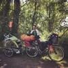 Un homme avec son chien et sa bicyclette chargée de bagages.