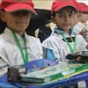 Deux enfants tiennent des jouets reçus en cadeau.