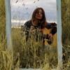 Le reflet d'Alexia Brazeau, armée de sa guitare acoustique, dans un miroir planté dans un champ