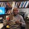 Gabriel Oba assis à son bureau.