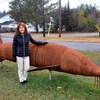 Gayle Primeau devant la sculpture en métal d'un immense esturgeon.