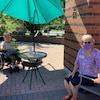 Deux femmes sont assises à l'extérieur et fixent la caméra. C'est l'été, il fait soleil et un parasol vert les protège des rayons.