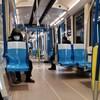 Deux personnes, dont une masquée, sont assises à bonne distance dans un wagon de métro vide.