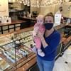 Une femme porte un masque et tient son bébé devant un présentoir de pâtisserie.
