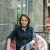 Assise sur une chaise solaire rose, elle sourit à la caméra.
