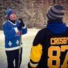 Deux joueurs de hockey discutent  sur une patinoire extérieure
